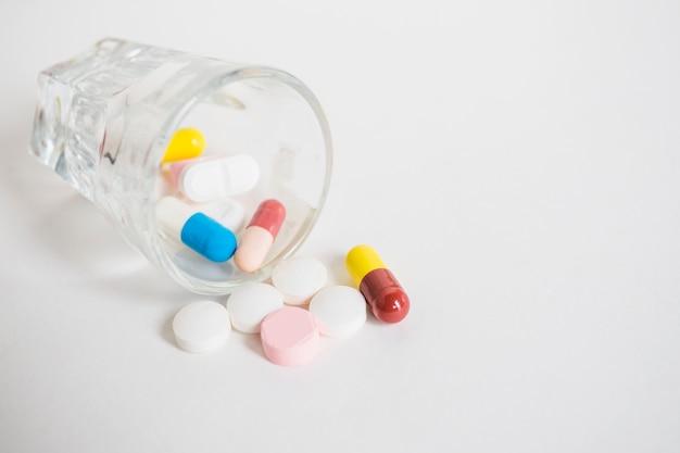 Beaucoup de pilules colorées renversant de minuscule verre sur fond blanc Photo gratuit