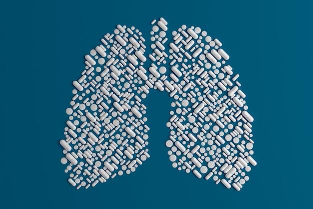 Beaucoup de pilules dispersées sur un bleu en forme de poumon Photo Premium