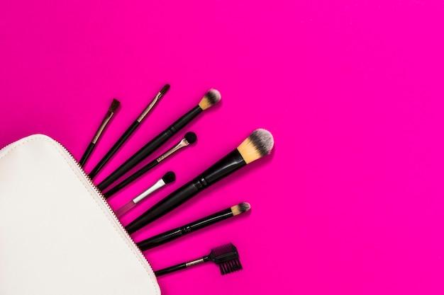 Beaucoup de pinceaux de maquillage en sac blanc sur le fond rose Photo gratuit