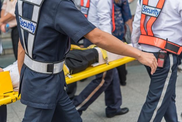 Beaucoup de travailleurs préparent un exercice d'incendie ou une autre catastrophe en déplaçant un patient blessé Photo Premium