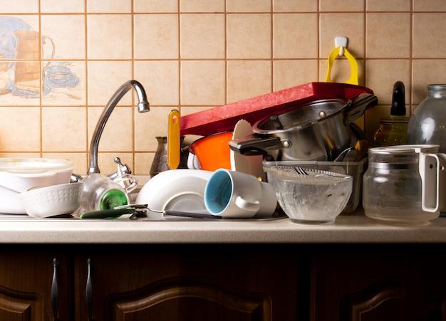 Beaucoup de vaisselle sale se trouve dans l'évier de la cuisine et doit être lavée. Photo Premium