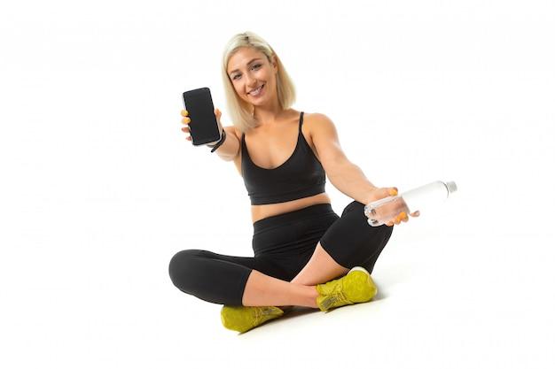Beauiful Sport Caucasian Girl Est Assis Sur Le Sol En Baskets Jaunes, Jambes Croisées, Montre Un Téléphone Mobile Et Garde Une Bouteille D'eau Isolée Photo Premium