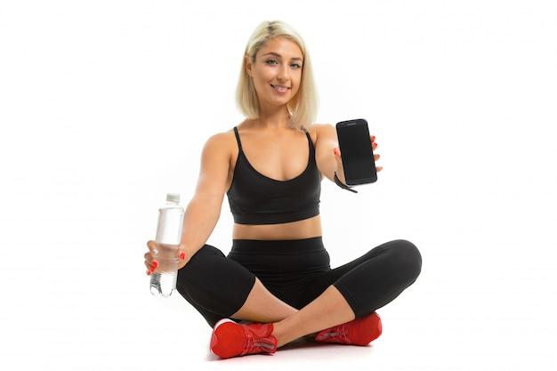 Beauiful Sport Caucasian Girl Est Assis Sur Le Sol En Baskets Res, Jambes Croisées, Montre Un Téléphone Mobile Et Garde Une Bouteille D'eau Isolée Photo Premium