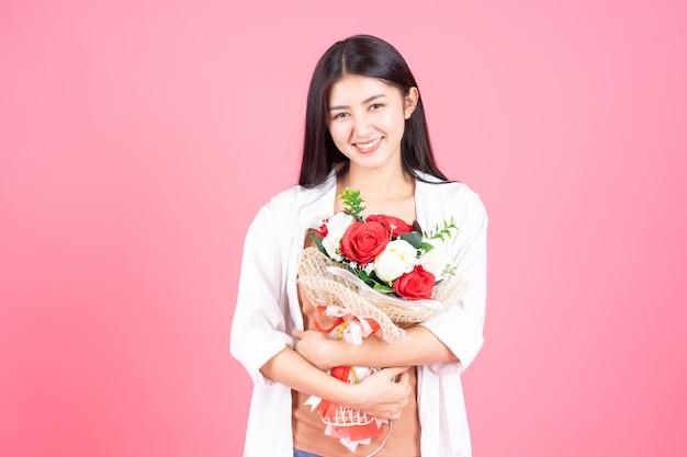 Beauté femme asiatique jolie fille se sentir heureux holding fleur rose rouge et rose blanche sur fond rose Photo gratuit