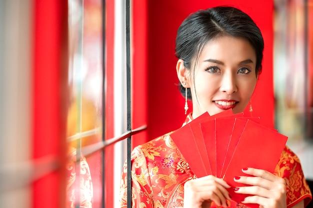 Beauté femme en robe rouge cheongsam traditionnel tenant des enveloppes rouges Photo Premium