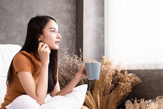 La beauté femme tenant une tasse de café en céramique dans la main, regardant par la fenêtre Photo Premium