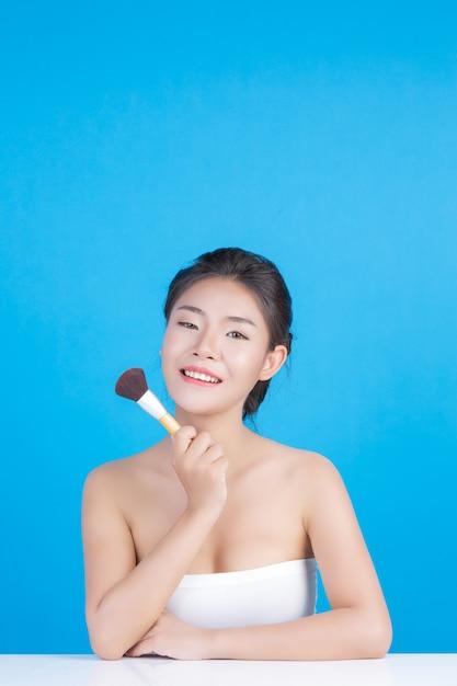 La beauté des femmes avec des images parfaites de la santé de sa peau toucher son visage et sourire comme un spa pour prendre soin de sa peau bleu Photo gratuit