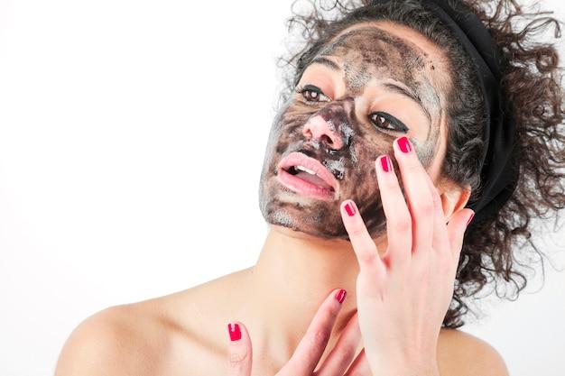 Beauté jeune femme à l'aide d'un masque noir isolé sur fond blanc Photo gratuit