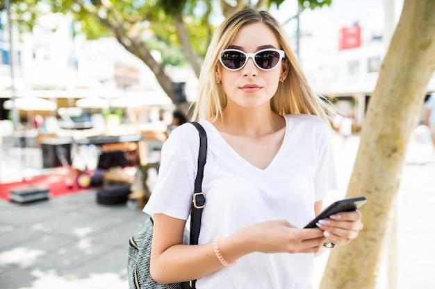 Beauté Jeune Femme à L'aide De Téléphone Intelligent à L'extérieur Dans La Rue Ensoleillée D'été Photo gratuit