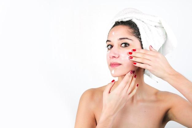 Beauté jeune femme appliquant la crème sur le visage isolé sur fond blanc Photo gratuit
