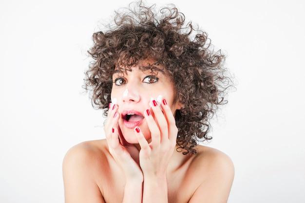 Beauté jeune femme avec une bouche ouverte, appliquant la crème sur son visage Photo gratuit