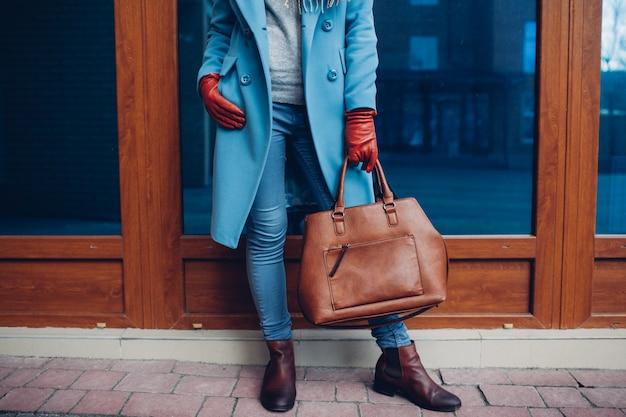 Beauté et mode. élégante femme à la mode portant manteau et gants, tenant un sac à main marron Photo Premium
