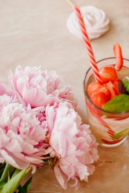 Beauté plat poser avec de l'eau de fraise désintoxication, accessoires et pivoines sur un fond de marbre Photo Premium