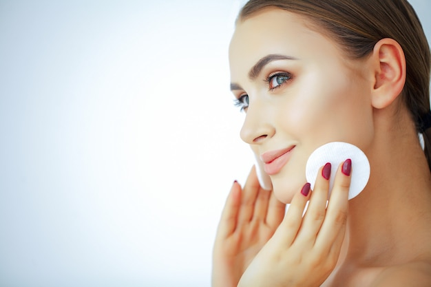 Beauté et soins. belle jeune femme à la peau pure. tient à la main des tampons de coton. portrait d'une femme avec un sourire. Photo Premium