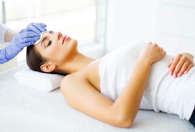 Beauté et soins. jeune fille avec une peau propre dans le salon spa. femme se détendre et se coucher avec les yeux fermés. haute résolution Photo Premium
