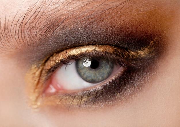 Beauté des yeux gros plan avec maquillage créatif couleurs yeux smokey noir et or Photo Premium