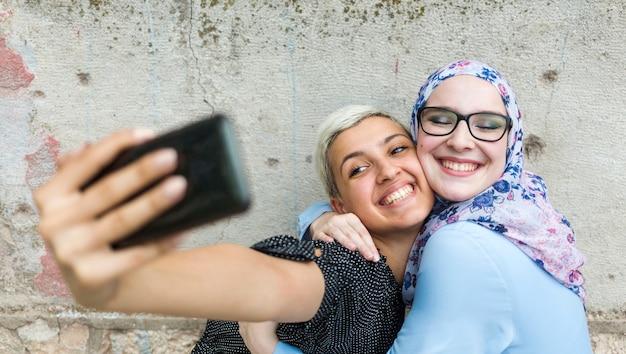 Beaux amis prenant un selfie Photo gratuit