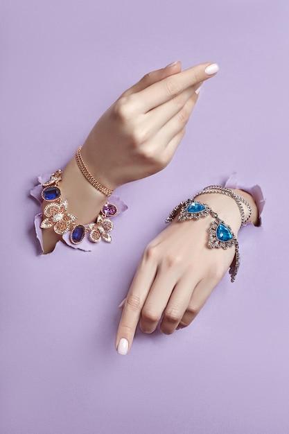 Beaux bijoux sur les mains des femmes, papier déchiré Photo Premium