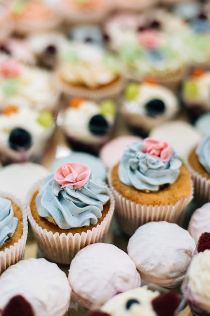 Beaux Cupcakes Colorés Et Desserts à La Crème Sur La Table De Restauration Pour La Fête Photo Premium