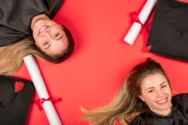 Beaux diplômés avec fond rouge Photo gratuit