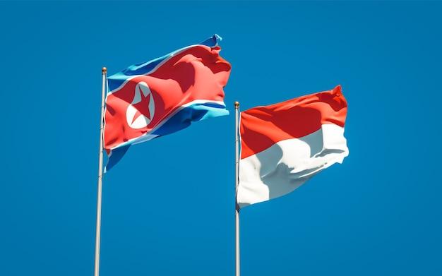Beaux Drapeaux D'état National De La Corée Du Nord Et De L'indonésie Ensemble Sur Ciel Bleu Photo Premium
