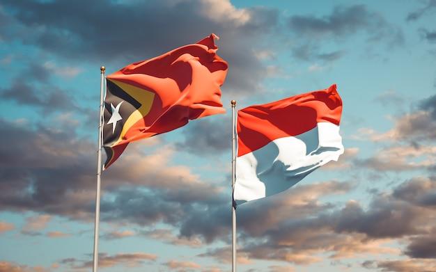 Beaux Drapeaux D'état National Du Timor Oriental Et De L'indonésie Ensemble Sur Ciel Bleu Photo Premium