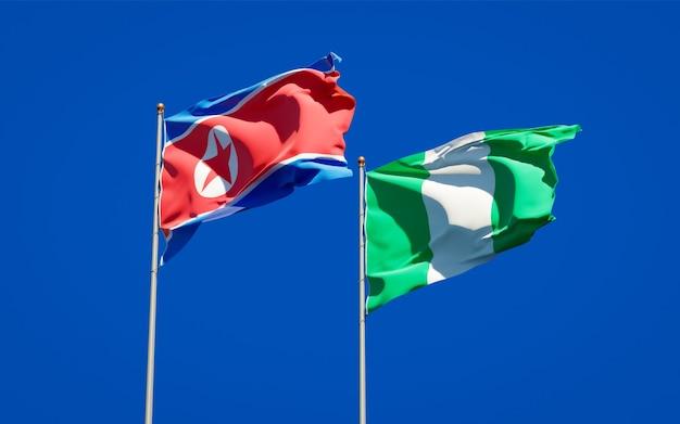 Beaux Drapeaux Nationaux De La Corée Du Nord Et Du Nigéria Ensemble Sur Ciel Bleu Photo Premium