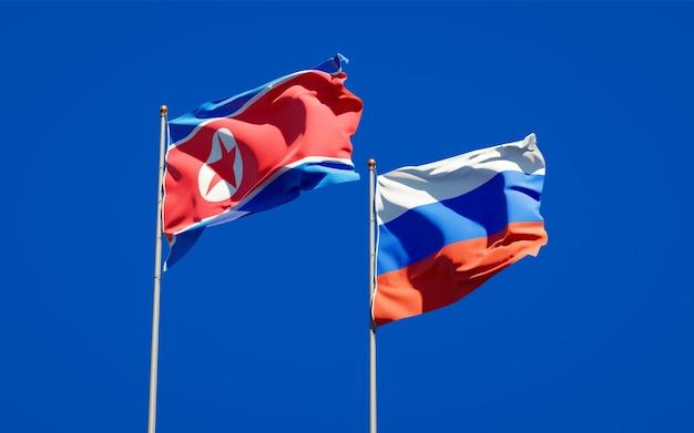 Beaux Drapeaux Nationaux De La Corée Du Nord Et De La Russie Ensemble Sur Le Ciel Bleu. Illustration 3d Photo Premium