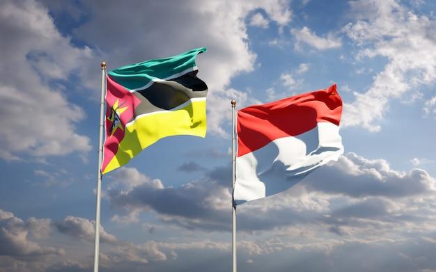Beaux Drapeaux Nationaux Du Mozambique Et De L'indonésie Ensemble Sur Ciel Bleu Photo Premium