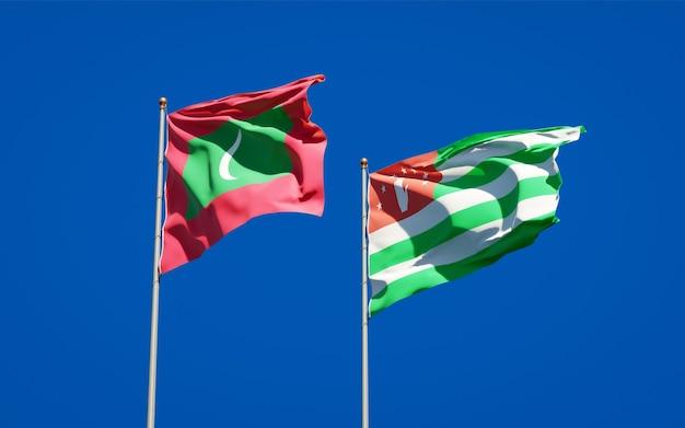 Beaux Drapeaux Nationaux Des Maldives Et De L'abkhazie Ensemble Sur Ciel Bleu. Illustration 3d Photo Premium