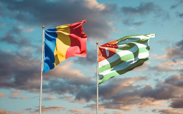 Beaux Drapeaux Nationaux De La Roumanie Et De L'abkhazie Ensemble Sur Le Ciel Bleu. Illustration 3d Photo Premium