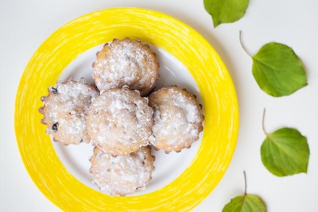 Beaux gâteaux avec du sucre en poudre sur une assiette jaune. Photo Premium