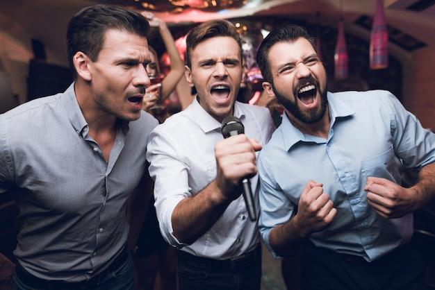 Beaux hommes chantent karaoké dans le club Photo Premium