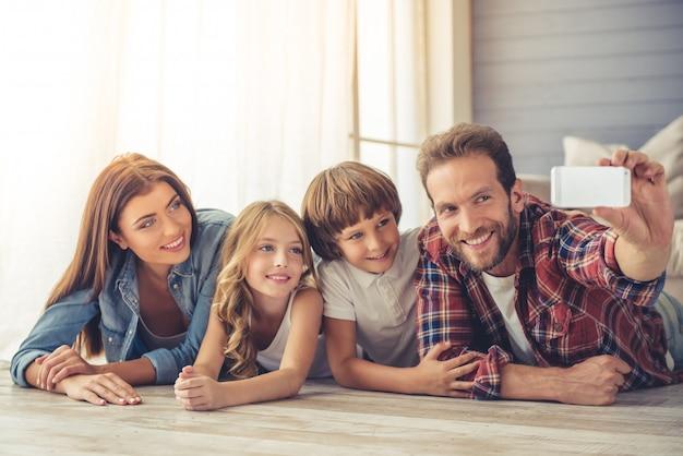 Beaux jeunes parents et leurs enfants font selfie Photo Premium