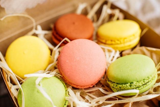 De beaux macarons multicolores dans une boîte en carton Photo Premium