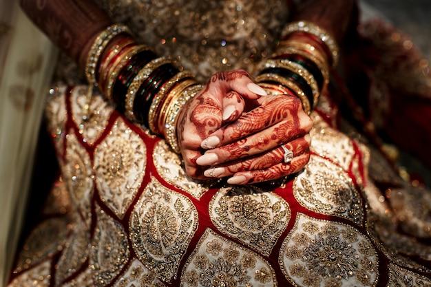 De beaux motifs de mehndi couvrent les doigts de la mariée qu'elle tient Photo gratuit