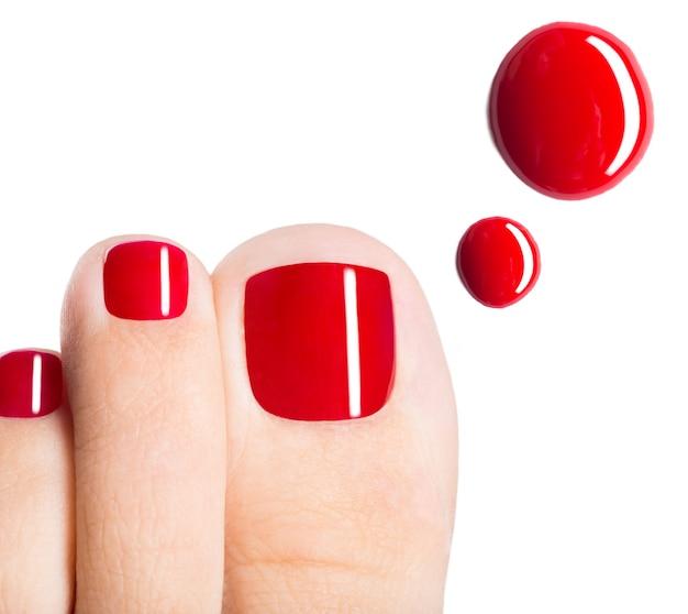 Beaux Orteils Féminins Avec Pédicure Rouge Et Gouttes De Vernis à Ongles Sur Un Espace Blanc Photo gratuit