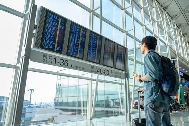 Les beaux touristes masculins utilisent les smartphones pour vérifier les vols avant d'embarquer. Photo Premium