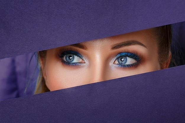 De beaux yeux de femmes regardent dans le trou de papier, un maquillage éclatant. Photo Premium