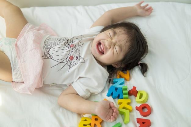 Bébé asiatique jouant des lettres abc sur un lit Photo Premium