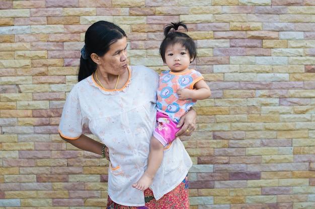 Bébé asiatique et mère sur la texture de fond de brique Photo Premium