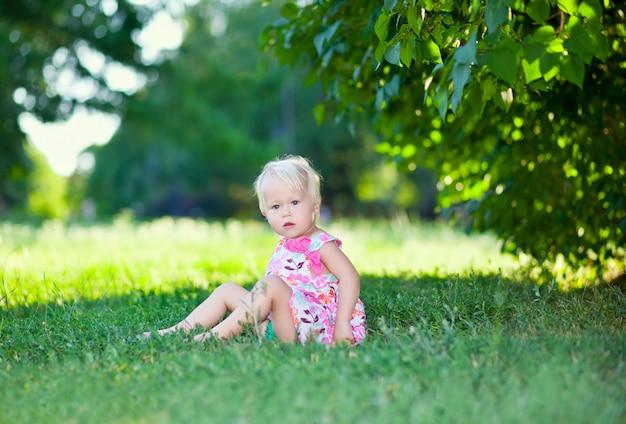 Bébé assis sur l'herbe verte Photo Premium
