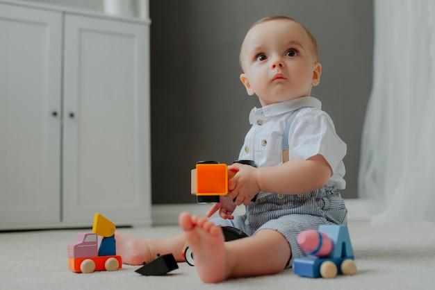 Bébé assis sur le sol avec des jouets et surpris. Photo gratuit
