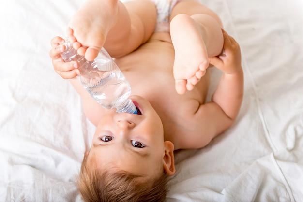 Bébé en bas âge allongé sur le lit blanc, sourit et boit de l'eau d'une bouteille en plastique Photo Premium