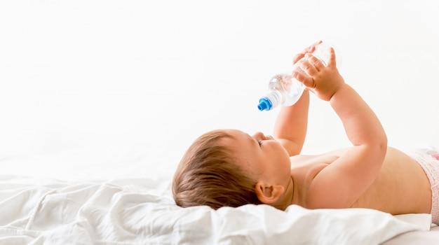 Bébé En Bas âge Est Assis Sur Le Lit Blanc, Sourit Et Boit De L'eau D'une Bouteille En Plastique Photo Premium