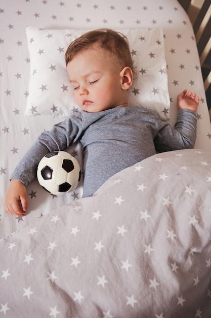 Le bébé dort dans un berceau avec un ballon de football à la main. Photo Premium