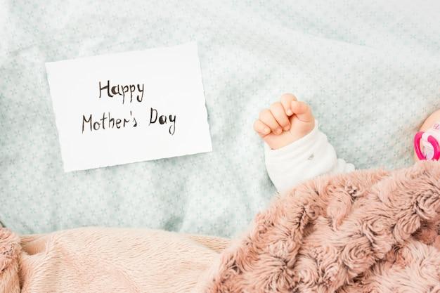 Bébé dort dans son lit près de l'inscription heureuse fête des mères Photo gratuit