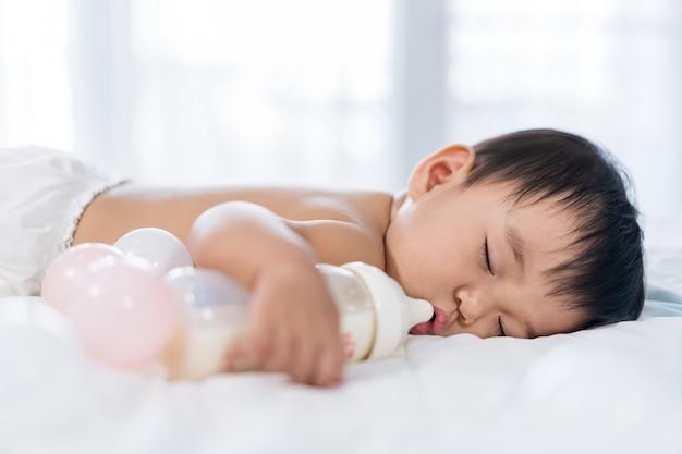 Bébé dort sur le lit après avoir bu une bouteille de lait Photo Premium
