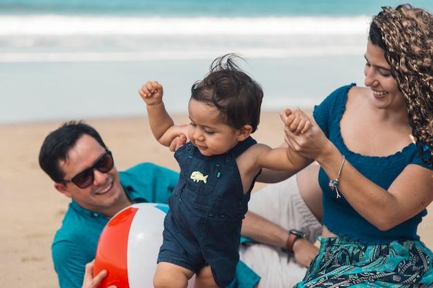 Bébé fait ses premiers pas avec sa mère au bord de la mer Photo gratuit
