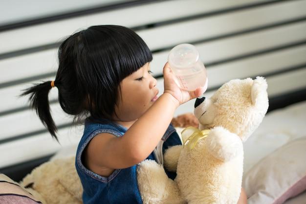 Bébé fille, jouer nounours, boire, lait, sur, lit Photo Premium